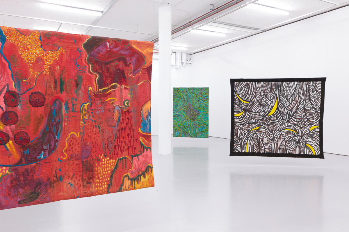 A series of abstract pain hang out from the ceiling of a brightly lit gallery